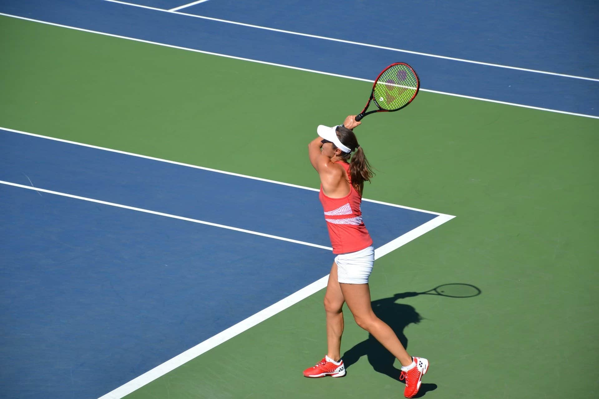 Common Tennis Questions - A person hitting a ball with a racket on a court - Tennis